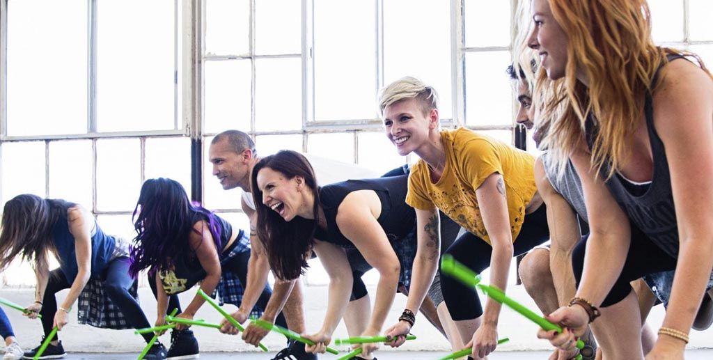 young adults hitting the ground with green drumsticks at a Pound class