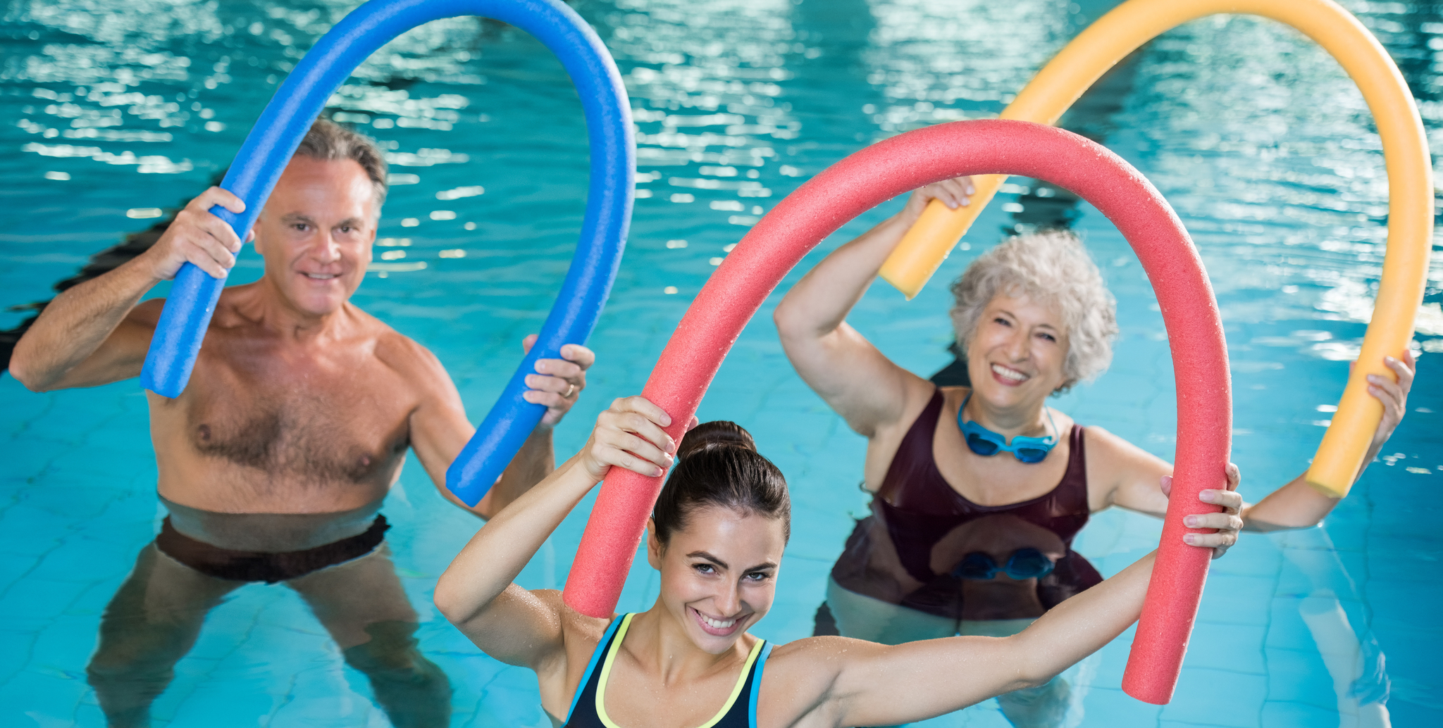 senior man, senior woman, and younger woman smiling while stretching with pool noodles during a water workout