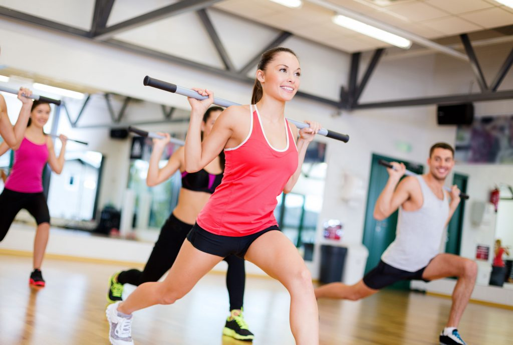 men and women smiling while lunging with a bar