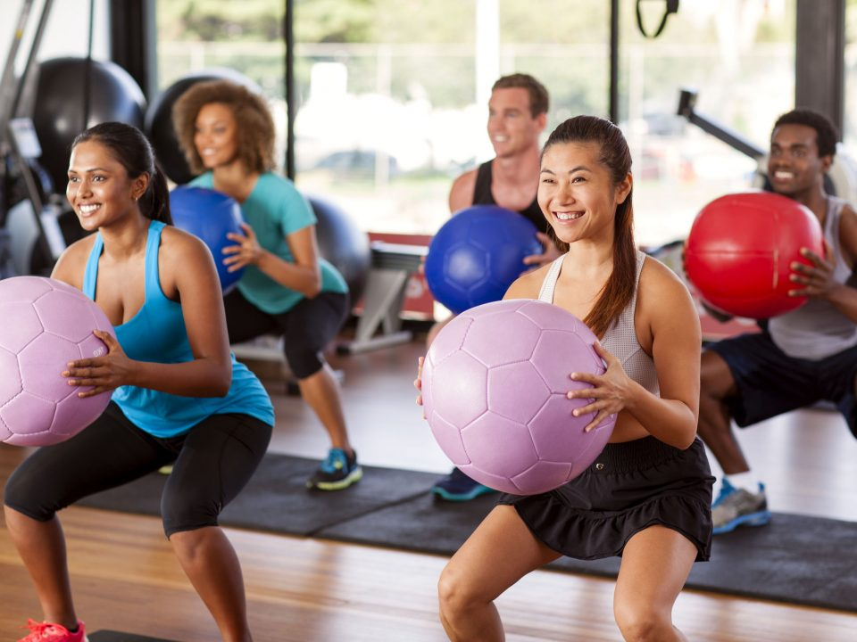 women and men squatting with exercise balls in a group fitness class