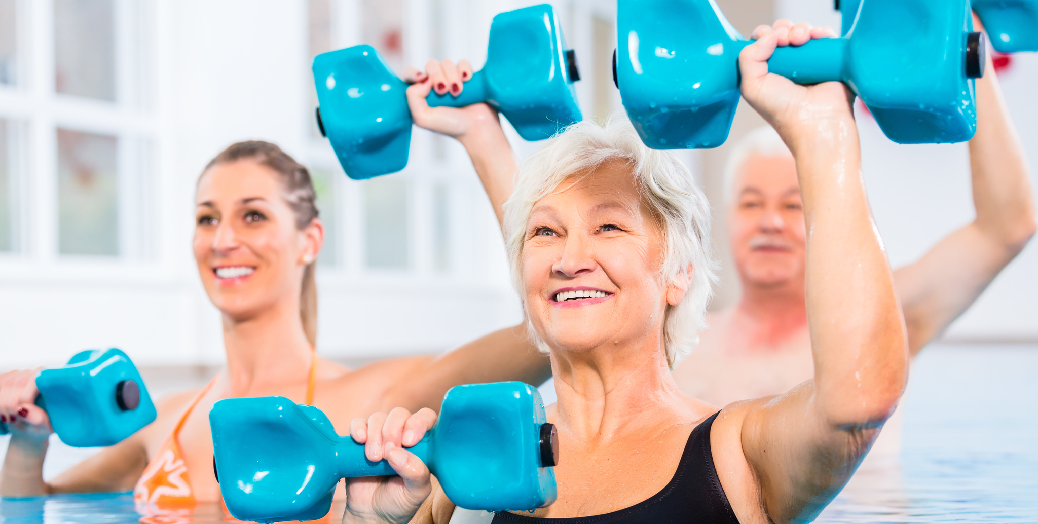 senior man and woman using small weights to tone muscles in the pool