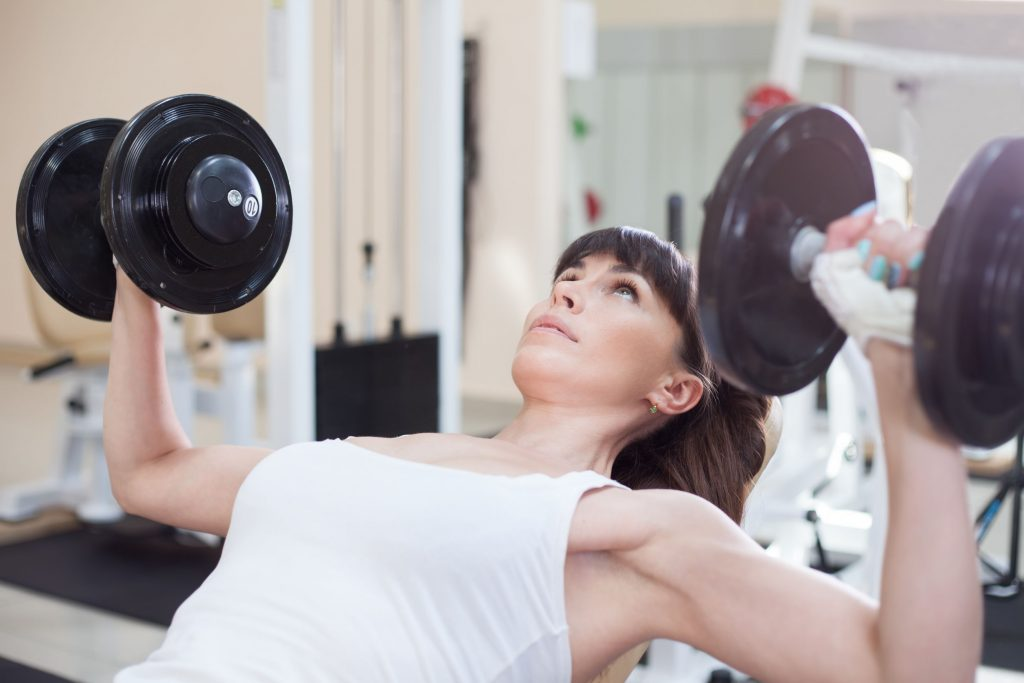 Woman lifting dumbells while seated on a bench at the gym