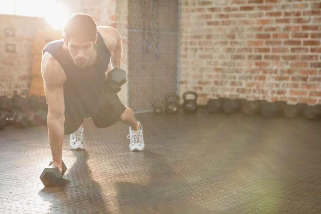 Focused man strength training by lifting dumbbells