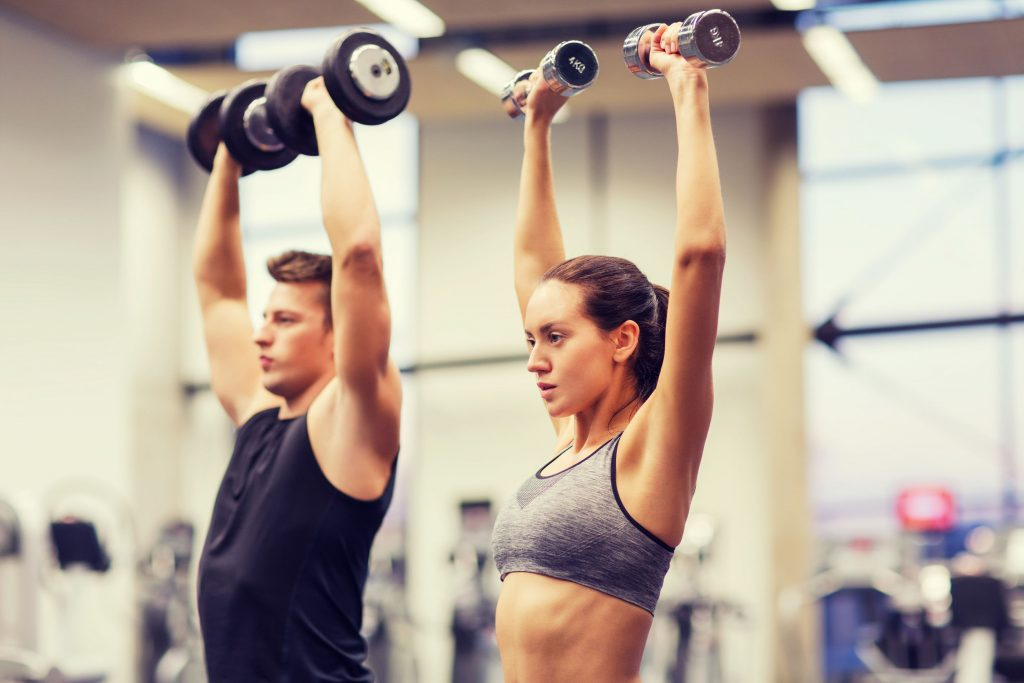 man and woman strength training with dumbbells