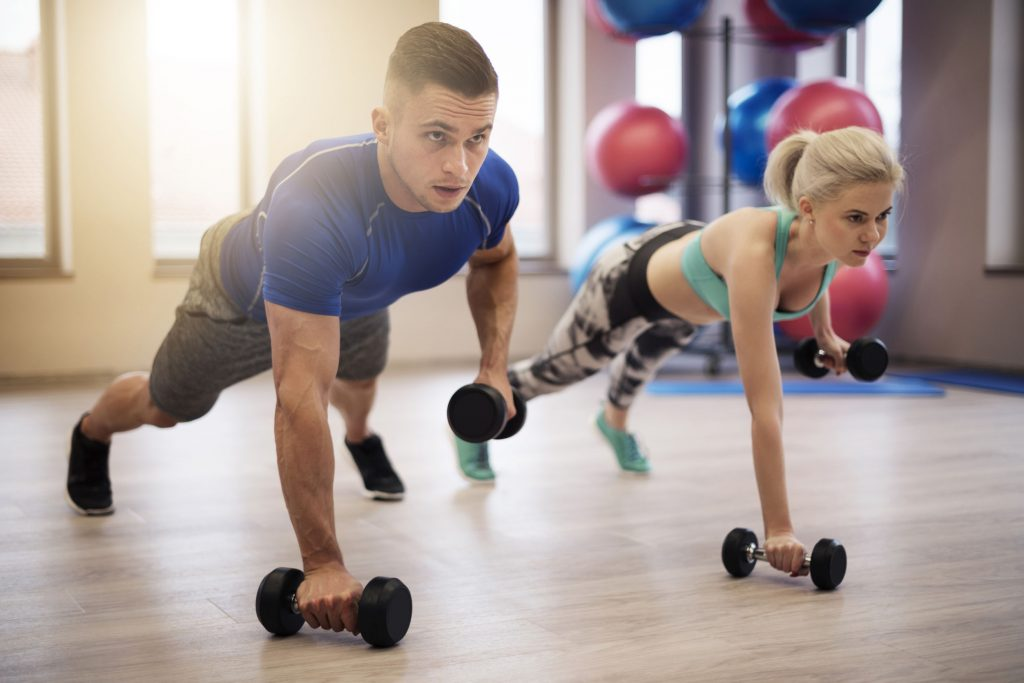 Couple working out together by doing push-ups with dumbbells