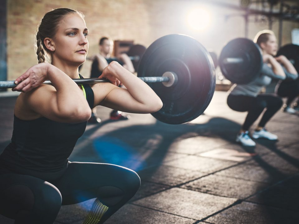 Woman strength training and squatting with a barbell