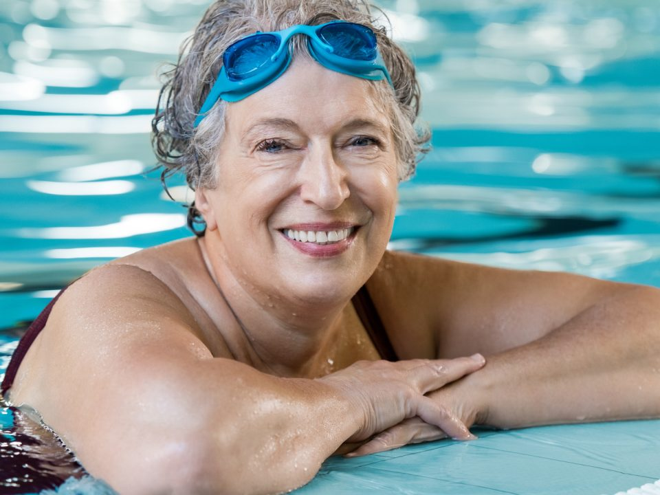 a senior woman smiling while in the pool during an aquatic group fitness class