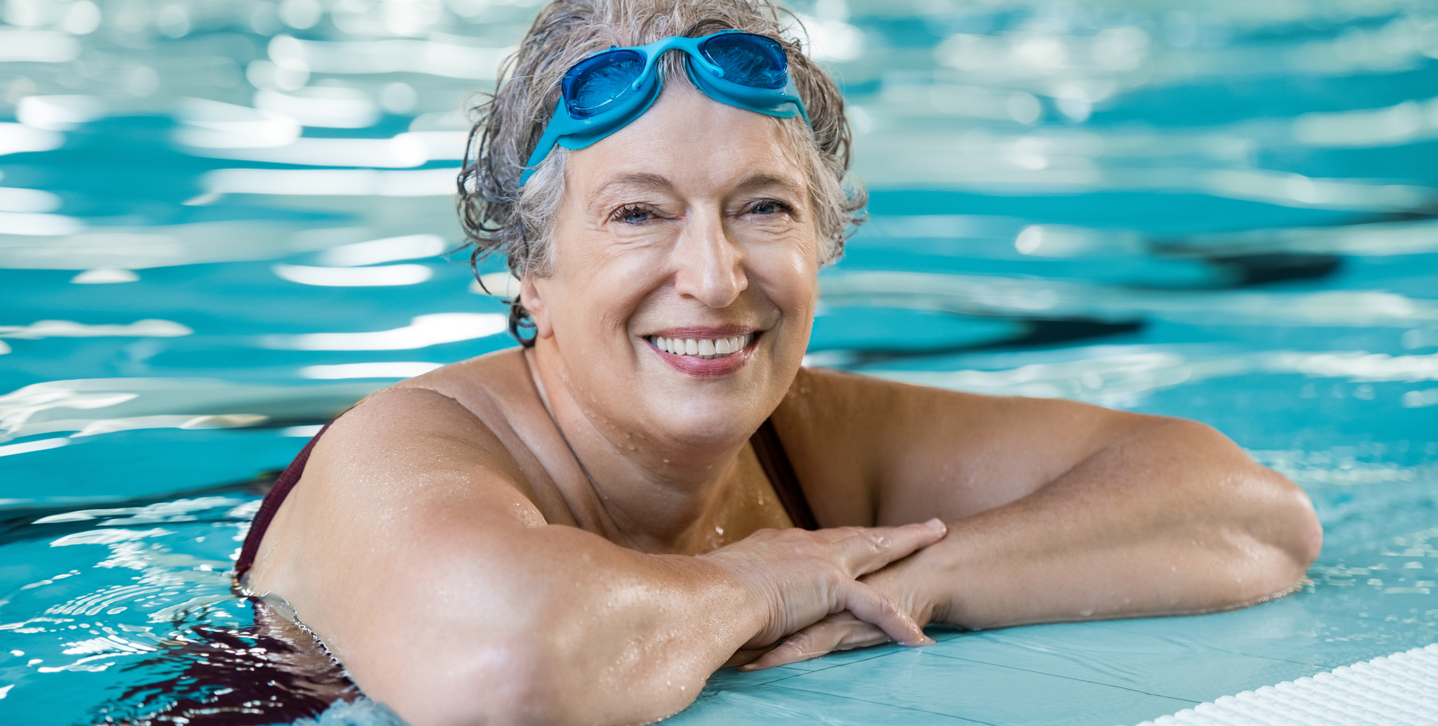 fit senior woman smiling while in the pool during a water workout
