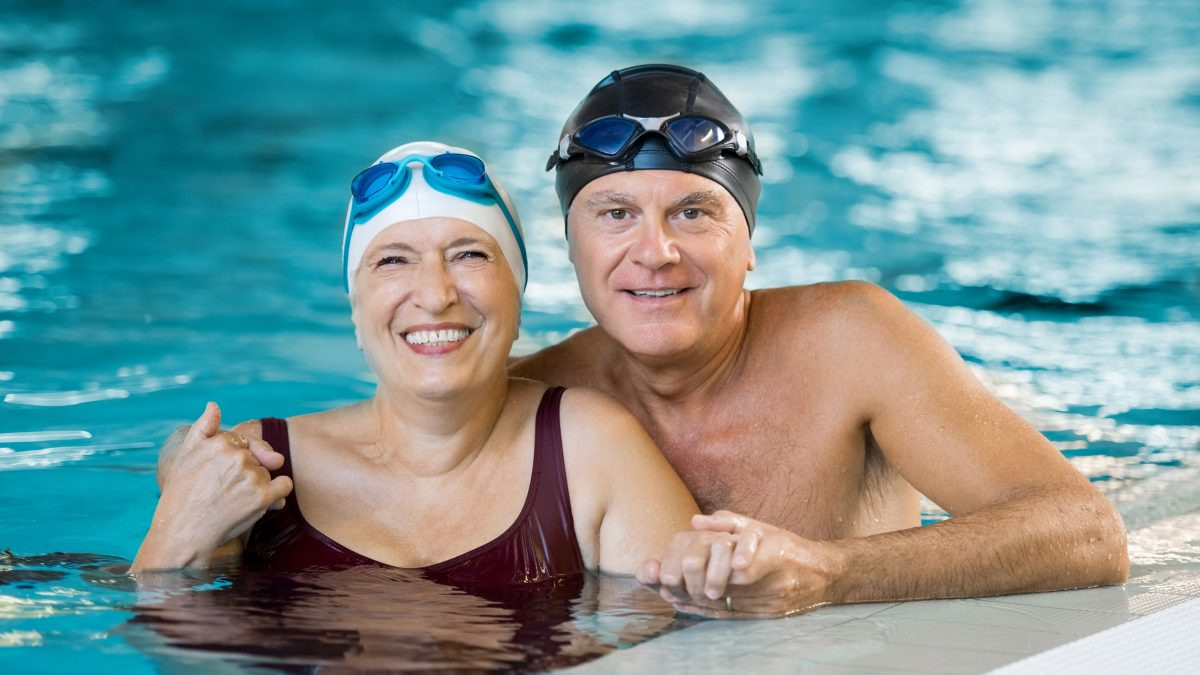 senior couple smiling while getting ready for an aquatics class