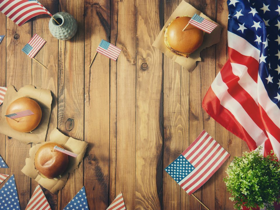 4th of July celebration with flags and burgers on a table
