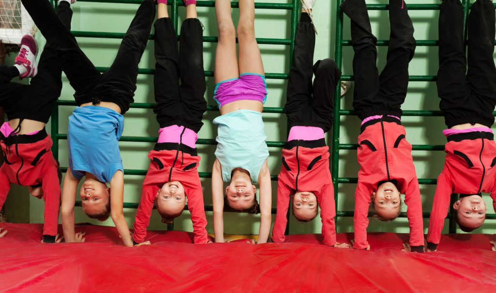 boys and girls doing handstands on a red gym mat