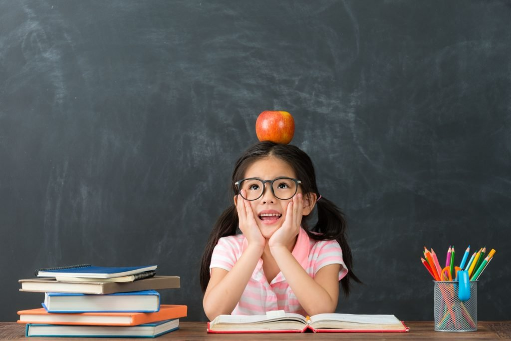 schoolgirl with pigtails and books, balancing an apple on her head in front of a chalkboard