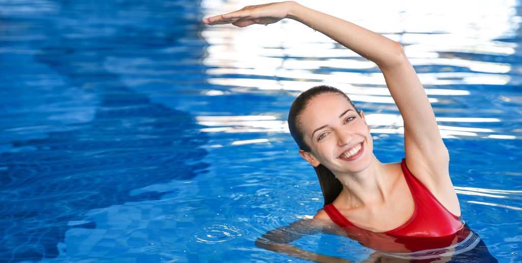 happy woman smiling while stretching in the pool during an aquatics class