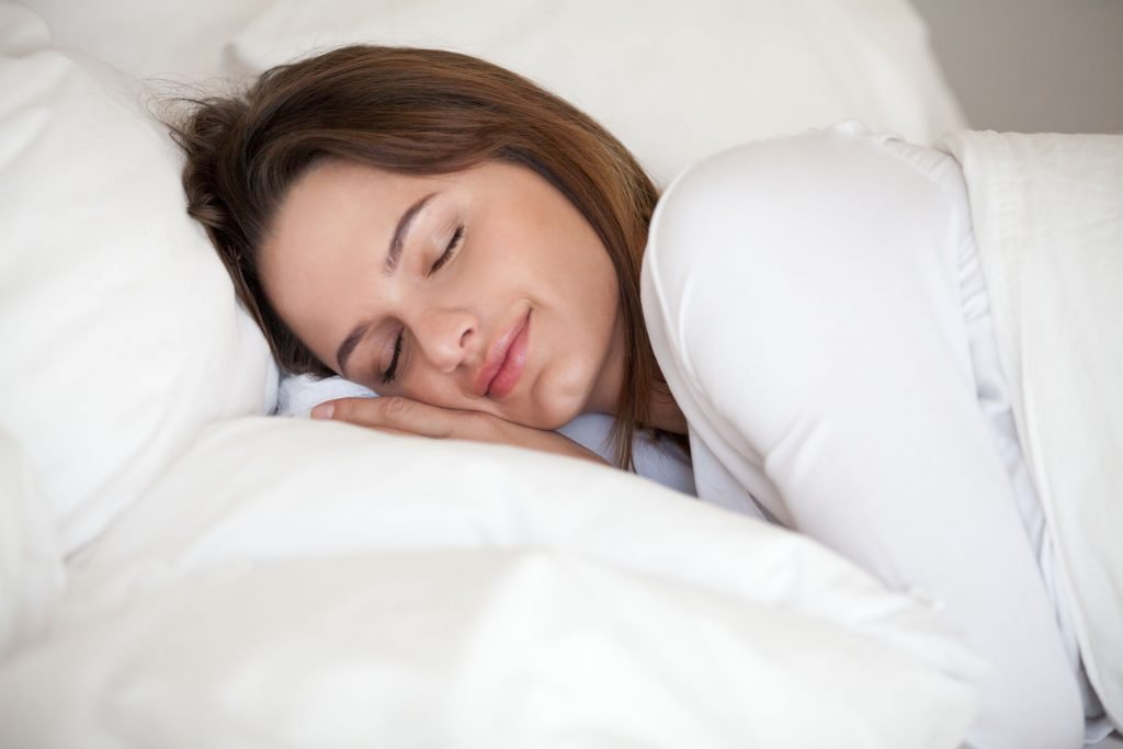 young woman sleeping under a white comforter
