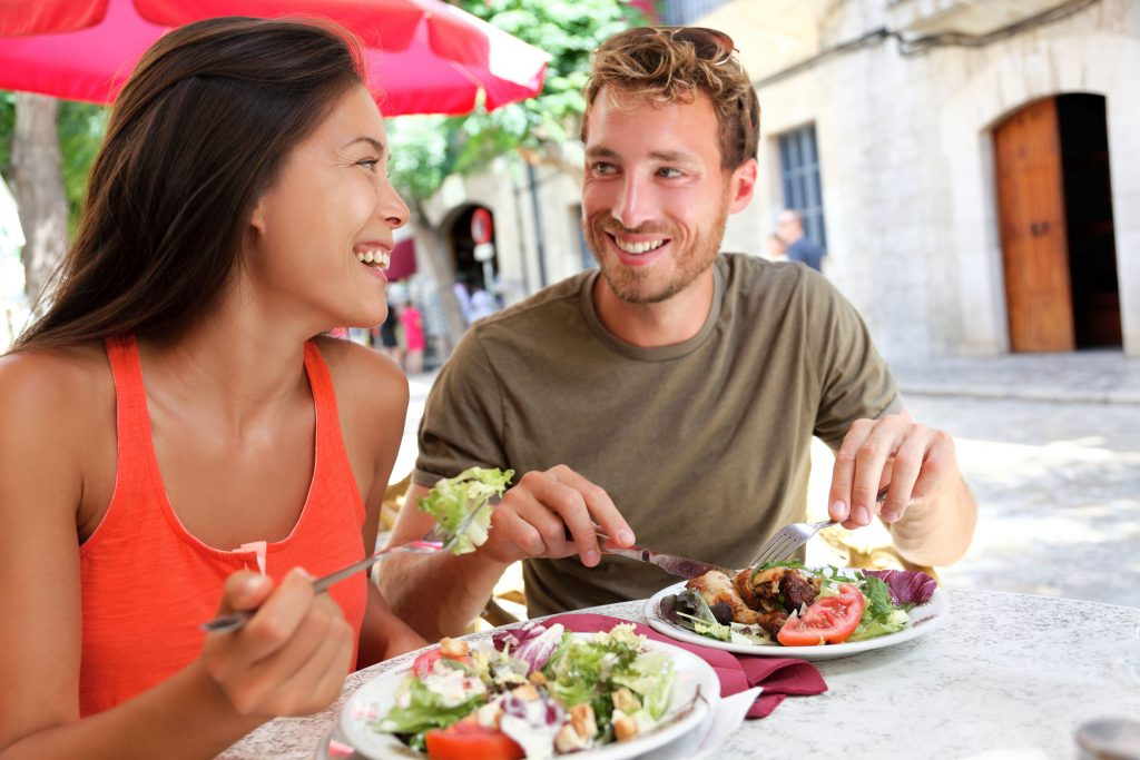 male and female college friends eating lunch together outdoors