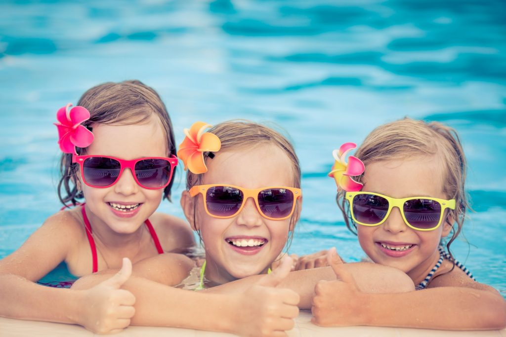three girls with sunglasses smiling in the pool after a swim lesson
