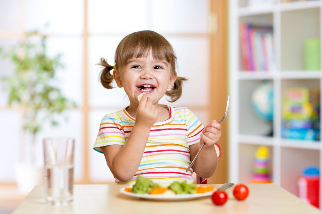 Alt: cute little girl eating broccoli, tomatoes, carrots, and other vegetables