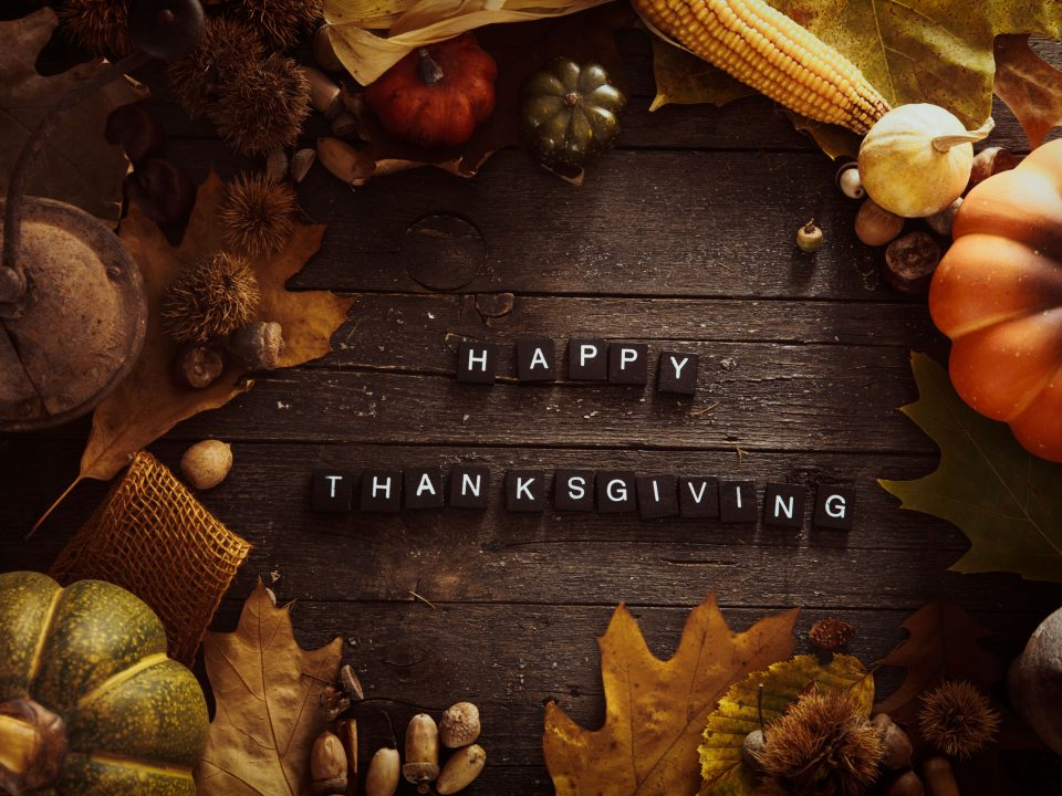 """fall fruits and vegetables on a wooden table with """"Happy Thanksgiving"""" letters"""
