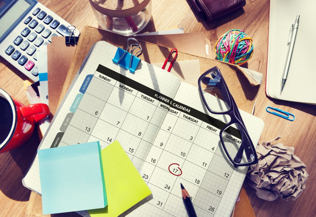calendar on desk with coffee, rubber band ball, pencil, sticky notes, and paper clips