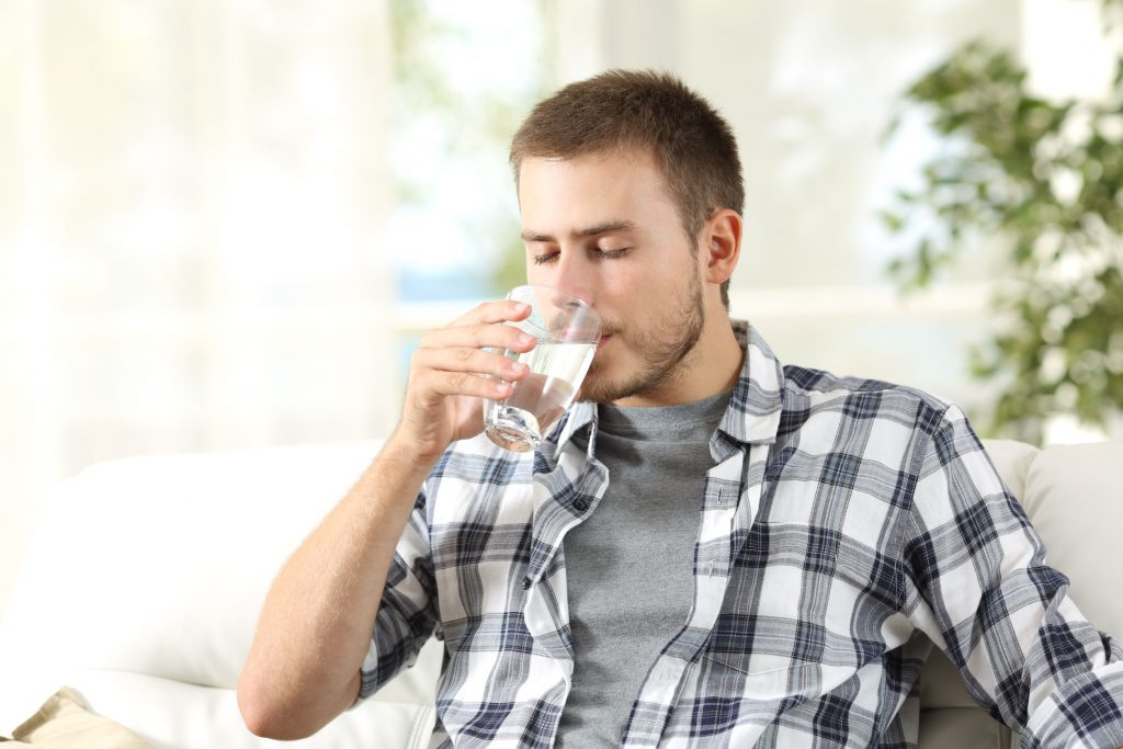 male college student drinking water while sitting on a couch