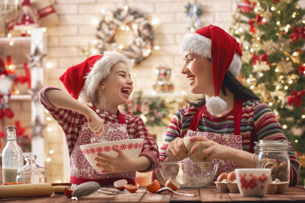 mom and daughter in Santa hats baking together by a Christmas tree