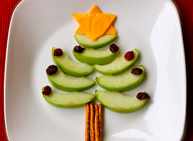 Christmas trees made from green apple slices, raisins for ornaments, pretzels for the trunk, and cheese for the star
