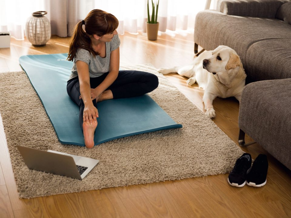 a woman stretching in her living room next to her dog