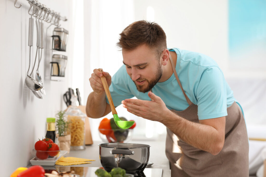 a man cooking soup in his kitchen