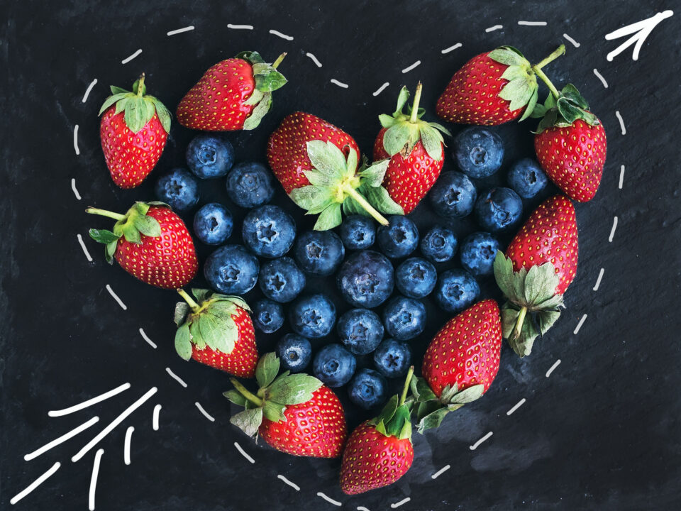 strawberries surrounding blueberries in a heart-shaped outline, symbolizing a healthy Valentine's Day