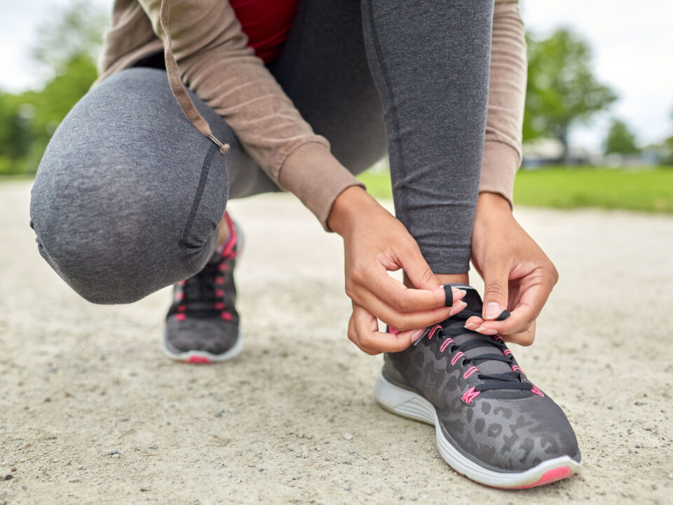 a woman tying her shoelaces before running outside in the spring