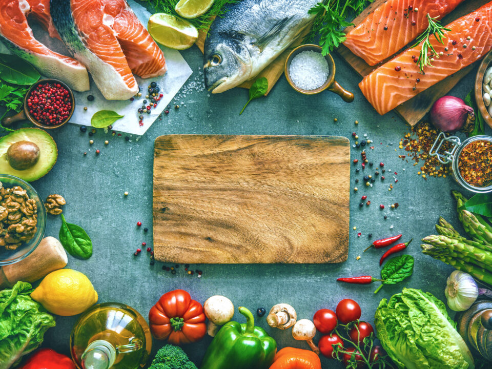low-cholesterol foods like salmon, avocados, tree nuts, lemons, and red bell peppers on a gray background