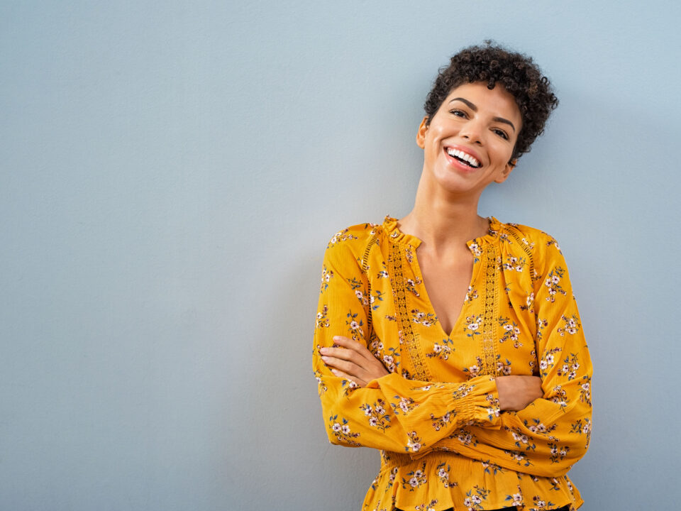 a smiling woman in a yellow top