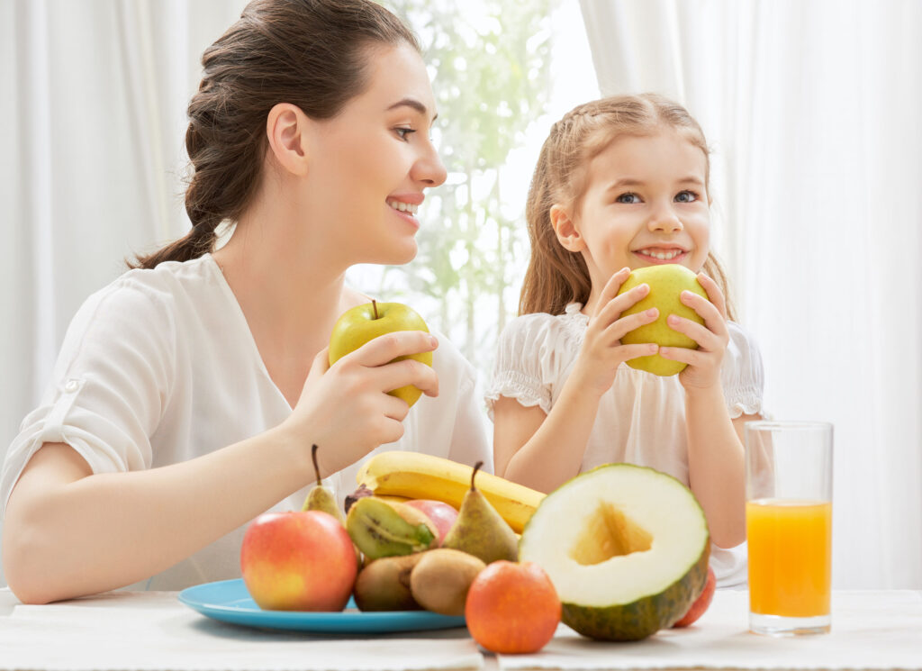 a mom and her daughter eating fresh fruit