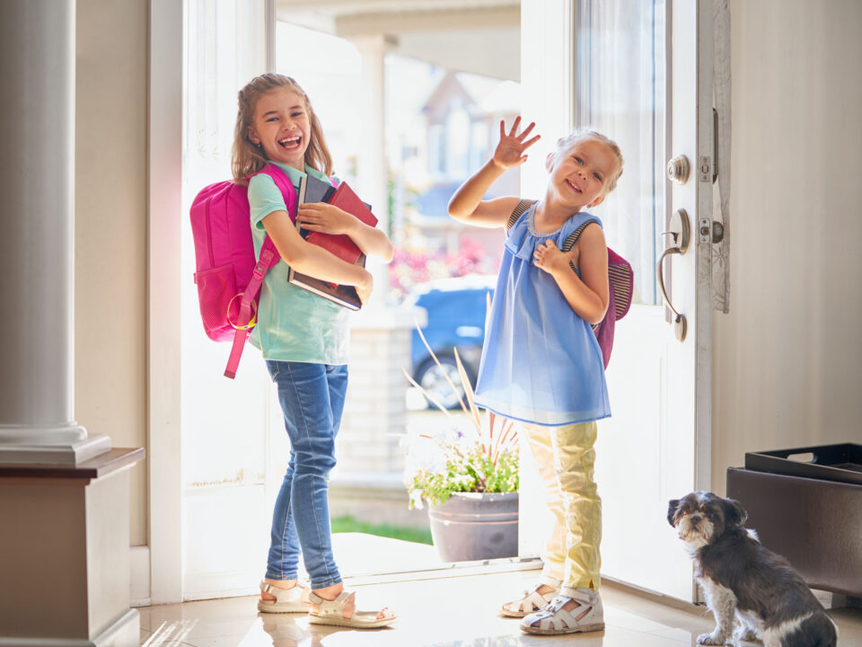 two girls with backpacks smiling and heading out the door to go to school